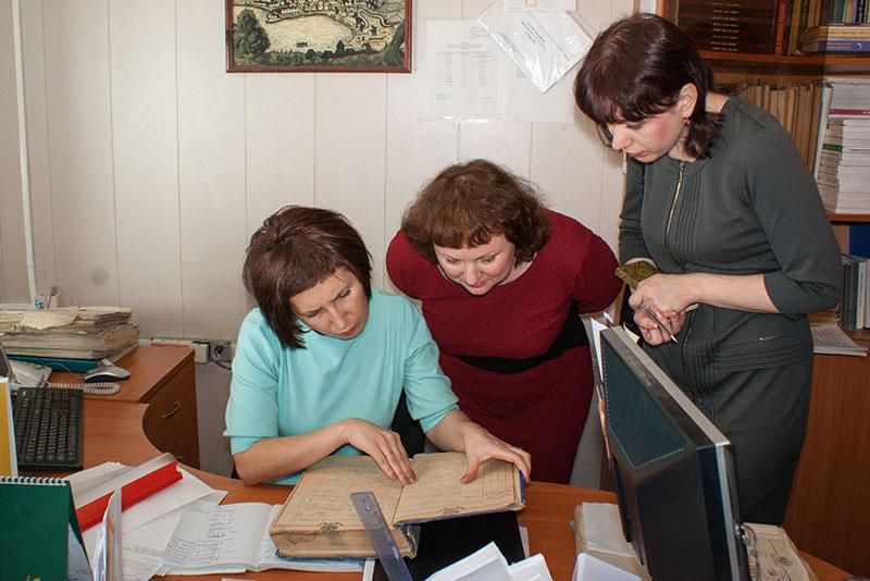 Сотрудник ГАСО показывает метрическую книгу директору НТГИА Т.А.Вязовой и главному хранителю фондов О.С.Репниковой. 2014 год.