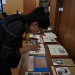Сотрудник Хэйлунцзянского архива Сунь Лэй изучает экспонаты выставки.